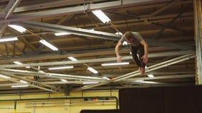 Um homem novo que olhe como trens de um dublê salta em um centro bronzeando-se vídeos de arquivo