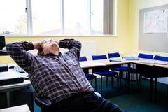 Um homem novo que relaxa em uma cadeira na parte dianteira de uma sala de aula 1 fotografia de stock royalty free