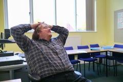 Um homem novo que relaxa em uma cadeira na parte dianteira de uma sala de aula fotografia de stock
