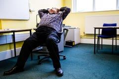 Um homem novo que relaxa em uma cadeira na parte dianteira de uma sala de aula fotos de stock