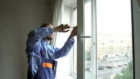 Um homem novo que repara uma janela vídeos de arquivo