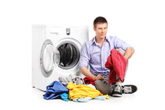 Um homem novo que senta-se ao lado de uma máquina de lavar Foto de Stock