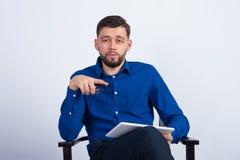 Um homem novo que senta-se com uma tabuleta branca Foto de Stock Royalty Free