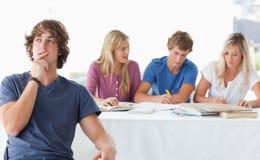 Um homem novo que senta-se na frente de do seus companheiros e pensamento de classe trabalhadora Fotos de Stock Royalty Free