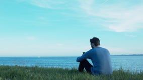 Um homem novo que senta-se na grama perto do mar escreve sms O barco está passando perto, o plano está voando no céu, a video estoque
