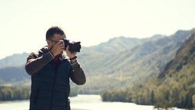 Um homem novo que toma fotos da natureza de Gorny Altai no seu Movimento lento filme