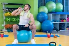 Um homem novo que toma uma ruptura no gym que senta-se em uma bola dos pilates com uma garrafa da água Fotografia de Stock