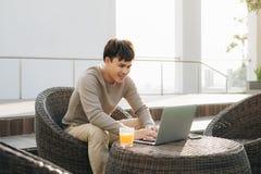 Um homem novo que usa o laptop ao sentar-se em um sof? fora fotos de stock royalty free