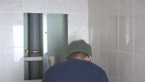 Um homem novo rasga fora uma telha em um banheiro devido a um escape em uma tubulação video estoque