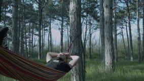 Um homem novo relaxa em uma rede na floresta Parzen com balanços de uma barba em uma rede Um homem novo de sono video estoque