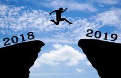 Um homem novo salta entre 2018 e 2019 anos sobre o sol e completamente na diferença da silhueta do monte Foto de Stock