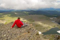 Um homem novo senta-se com os pés descalços com um portátil em seu trabalho de mãos como um f fotografia de stock royalty free