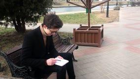 Um homem novo senta-se em um banco e faz-se esboços em um caderno filme