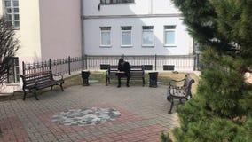 Um homem novo senta-se em um banco e faz-se esboços em um caderno video estoque