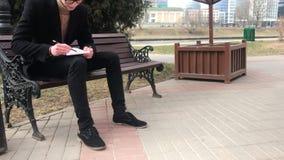 Um homem novo senta-se em um banco e faz-se esbo?os em um caderno vídeos de arquivo
