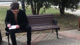 Um homem novo senta-se em um banco e faz-se esbo?os em um caderno video estoque