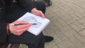 Um homem novo senta-se em um banco e faz-se esbo?os em um caderno filme
