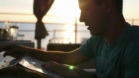 Um homem novo senta-se em um café e seleciona-se o alimento do menu, na perspectiva de um por do sol bonito no horizonte filme