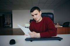 Um homem novo senta-se em uma cadeira do escritório, guardando um papel e uns olhares confundidos na câmera Fotos de Stock