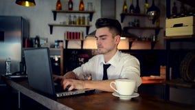 Um homem novo senta-se na cozinha no contador da barra e trabalha-se em um portátil filme