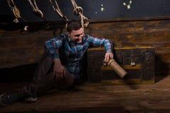 Um homem novo senta-se perto de uma caixa, olhando na garrafa de vidro e no tr fotografia de stock royalty free