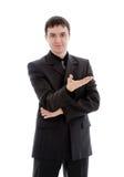 Um homem novo, sorrindo em um terno mostra uma mão. Fotografia de Stock Royalty Free
