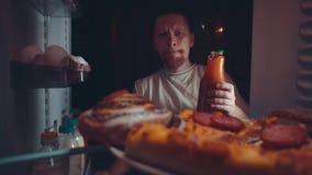 Um homem novo toma o alimento do refrigerador na noite video estoque