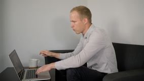 Um homem novo trabalha em um portátil que senta-se em um sofá preto video estoque
