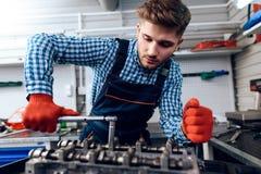 Um homem novo trabalha em uma estação do serviço O mecânico é contratado em reparar o carro Imagem de Stock