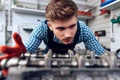Um homem novo trabalha em uma estação do serviço O mecânico é contratado em reparar o carro Fotografia de Stock Royalty Free