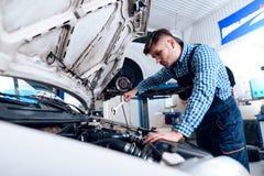 Um homem novo trabalha em uma estação do serviço O mecânico é contratado em reparar o carro Fotos de Stock Royalty Free