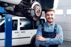 Um homem novo trabalha em uma estação do serviço O mecânico é contratado em reparar o carro Imagem de Stock Royalty Free