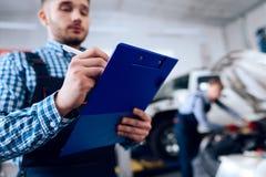Um homem novo trabalha em uma estação do serviço O mecânico é contratado em reparar o carro Foto de Stock