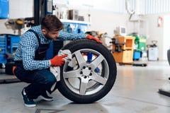 Um homem novo trabalha em uma estação do serviço O mecânico é contratado em reparar o carro Imagens de Stock Royalty Free
