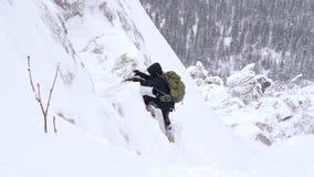 Um homem novo, um turista, com uma trouxa em seus ombros aumenta à parte superior de uma montanha coberto de neve filme