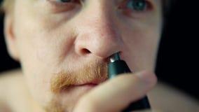 Um homem novo usa um ajustador bonde para remover o cabelo de seu nariz filme
