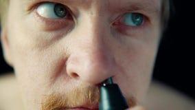 Um homem novo usa um ajustador bonde para remover o cabelo de seu nariz vídeos de arquivo