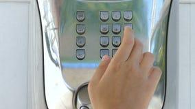 Um homem novo usa um payphone video estoque