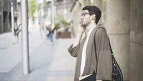 Um homem novo vestiu-se na roupa ocasional que fala no telefone Imagem de Stock Royalty Free