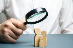 Um homem olha através de uma lupa em uma figura da família O estudo da composição de família e da situação demográfica estatístic imagens de stock