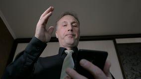 Um homem olha o correio no smartphone Obtém más notícias, viram-nas muito Vista da câmera da parte inferior vídeos de arquivo