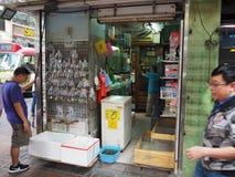 Um homem olha os peixes diferentes que são oferecidos para a venda em uma loja situada em Tung Choi fotografia de stock