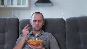 Um homem olha a tevê e come microplaquetas vídeos de arquivo