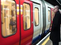 Um homem olha uma estação do estofamento da licença do trem no subterrâneo de Londres vídeos de arquivo