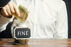 Um homem põe dólares em um frasco de vidro com a multa da palavra Dinheiro de salvamento e pagar uma multa Punição para um crime  fotografia de stock