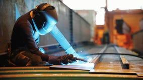 Um homem põe sobre uma máscara protetora e trabalhos com uma máquina de solda video estoque