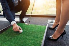 Um homem põe uma bola de golfe na frente de uma senhora do negócio em um terno restrito Uma mulher que prepara-se para um sopro Imagens de Stock