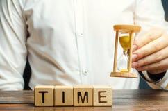 Um homem p?e blocos de madeira com o tempo de palavra Conceito da gest?o de tempo e da distribui??o apropriada Neg?cio e trabalho fotografia de stock royalty free