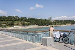 Um homem para baixo à cruz olha a água azul claro e os restos no ciclismo Fotografia de Stock Royalty Free