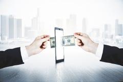 Um homem passa um outro dinheiro do homem através do smartphone, dinheiro em linha fotografia de stock royalty free